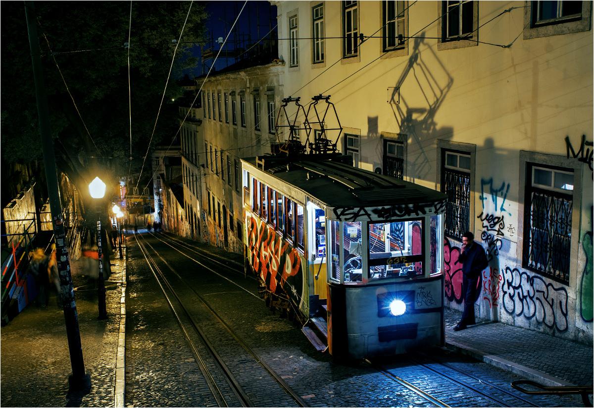 Motorniczy lizbońskiego funikularu Glória pali papierosa, oczekując na kolejny kurs w dół