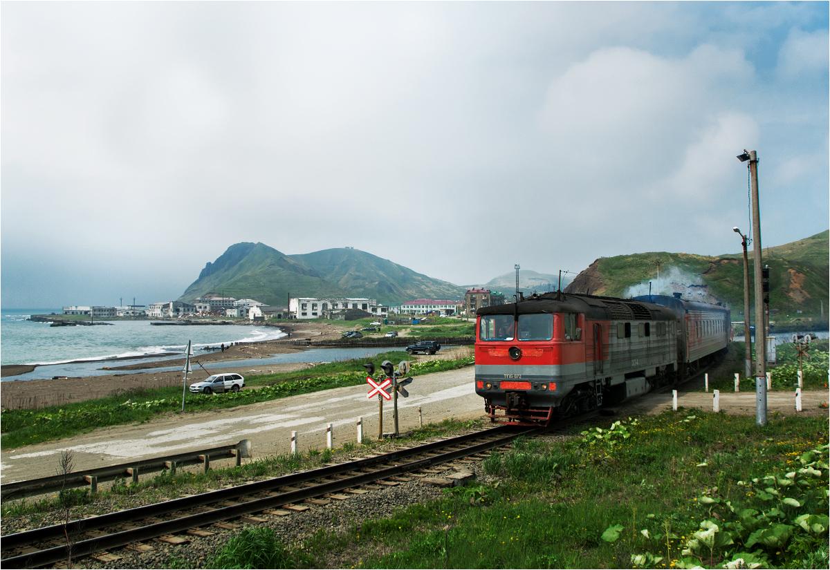 Na wpół martwe miasto Czechow przegląda się w wodach Morza Japońskiego. A na pierwszym planie przemyka pociąg osobowy do Chołmska prowadzony lokomotywą TG16