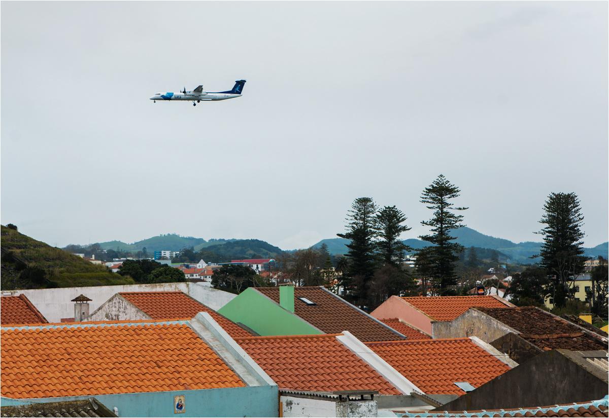 A Bombardier Q400 linii SATA podchodzi do lądowania ponad dachami domów