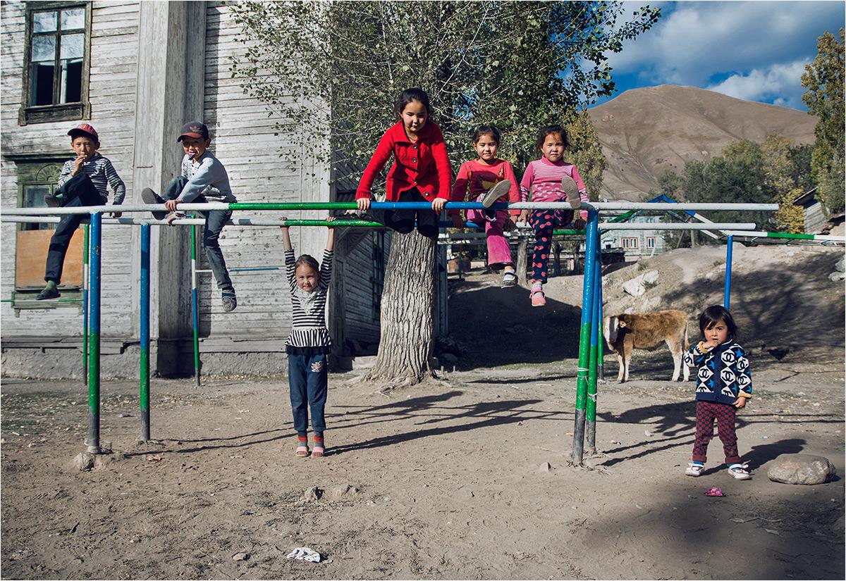 Dzieci bawiące się przed opuszczoną szkołą w Min-Kuszu
