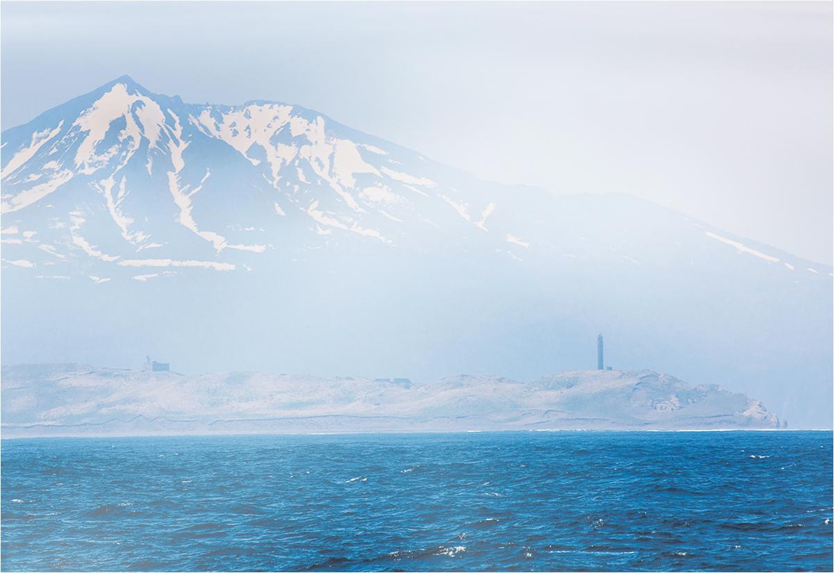 Wyspa Kunaszyr wynurza się zza mgieł i chmur. Przybyłych wita przylądek Łowcowa wraz z opuszczoną latarnią morską. W tle wznosi się wulkan Ruruj