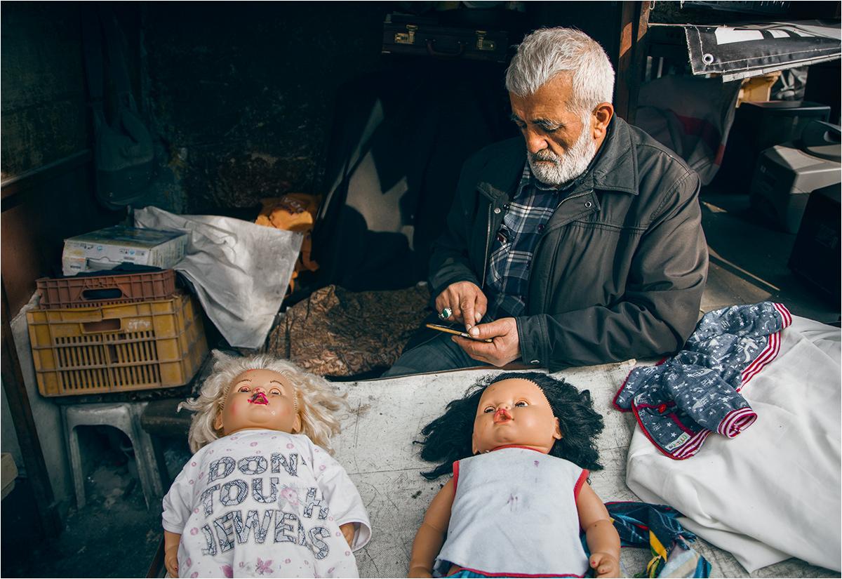 Mężczyzna sprzedający trupy lalek na pchlim targu w Ankarze