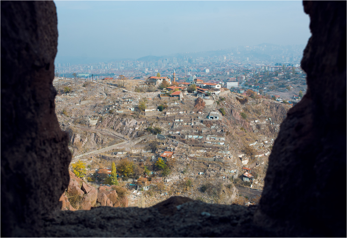Widok przez mury miejskie na wyburzane stare dzielnice miasta