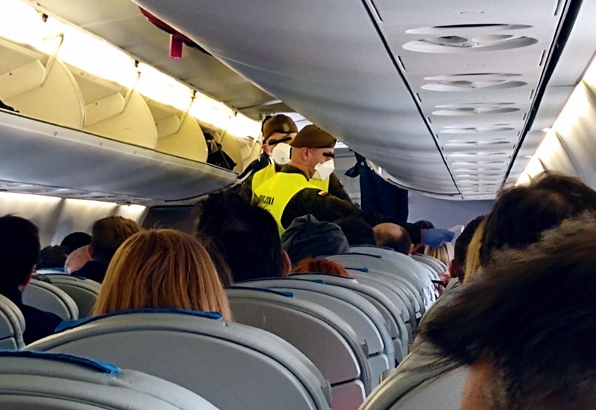 Żołnierze Wojsk Obrony Terytorialnej mierzą temperaturę pasażerom przylatującym na lotnisko Okęcie