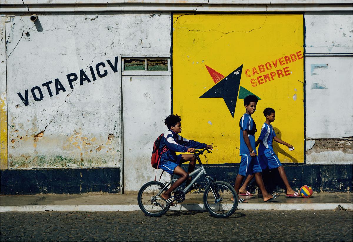 """Młodzi chłopcy z miasta Espargos mijają mural z napisem """"głosuj na PAICV"""". To skrótowiec od """"Partido Africano da Independência de Cabo Verde"""" (""""Afrykańska Partia na rzecz Niepodległości Zielonego Przylądka""""). PAICV rządziła krajem przez większość jego niepodległego istnienia, obecnie znajduje się w opozycji"""