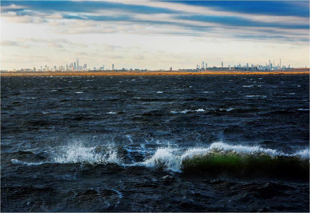 Sztormowe fale rozbijają się o brzeg półwyspu Rockaway. Daleko w tle rozciąga się panorama Manhattanu. Miejski skyline widać dość wyraźnie, ale to naprawdę kawał drogi...