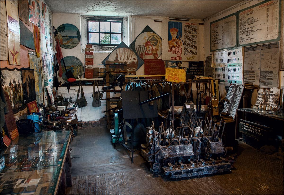 Izba Muzealna w prywatnym garażu. Na pierwszym planie widać wyciągnięty z ziemi silnik od czołgu