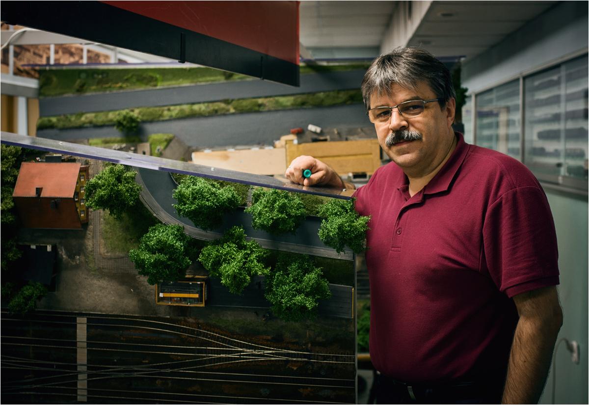 Piotr Karwatka, opiekun makiety stacji Międzychód, pozuje do zdjęcia z podniesionym fragmentem dioramy. To czas na wykonanie prac pod spodem stołu!