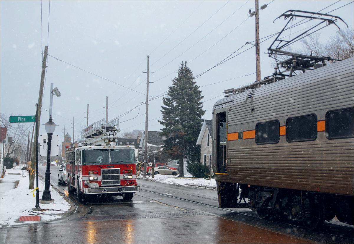 Widok prawie jak z amerykańskiego serialu o życiu prowincji - pociąg mija się z klasycznym czerwonym wozem strażackim