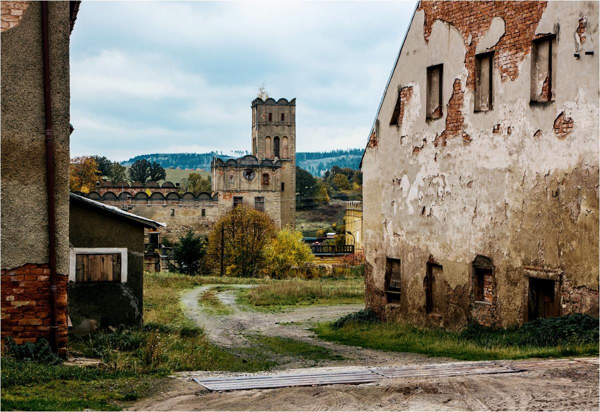 Zamek w Ratnie Dolnym widoczny spomiędzy dawnych zabudowań gospodarskich
