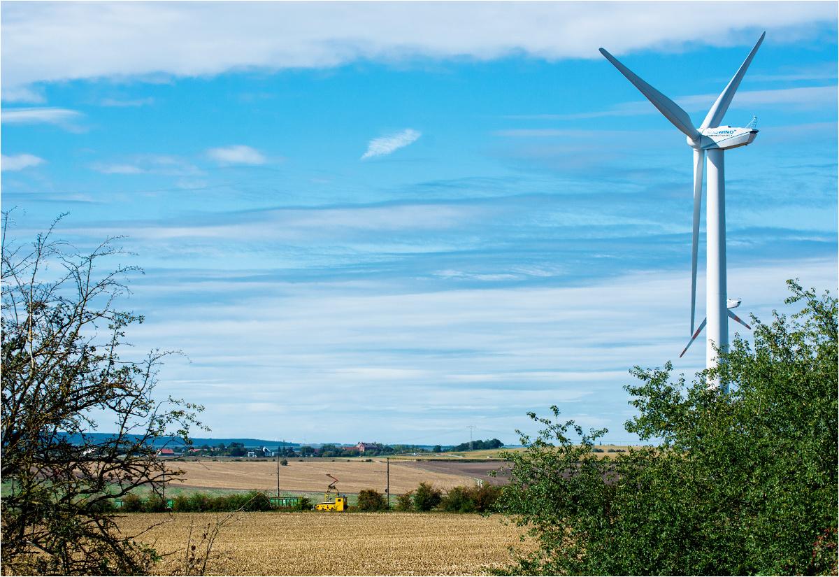 Pociąg kolejki sodowej zbliża się do elektrowni wiatrowej - symbolu współczesnego niemieckiego krajobrazu. Technologia lat minionych versus technologia przyszłości. Gospodarka rabunkowa kontra odnawialne źródła energii...