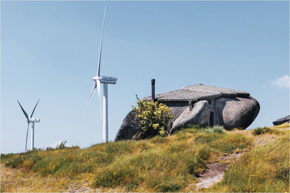 Kamienny dom na tle pobliskich elektrowni wiatrowych